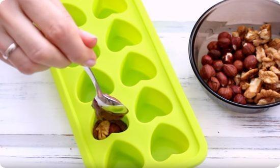 в формочки раскладываем орехи, заливаем шоколадом