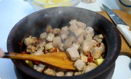 Выкладываем лук и морковку, а затем слой мяса в горшочек