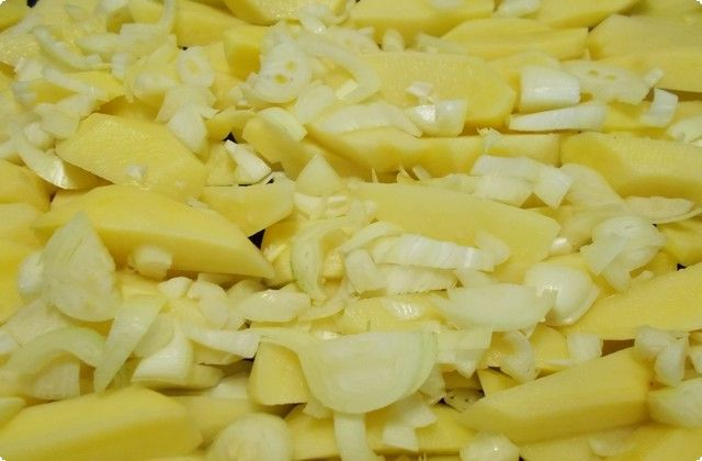 Нарезать лук на произвольные кусочки и посыпать им картошку