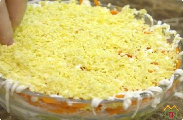 Трем на мелкой терке желтки, посыпаем салат