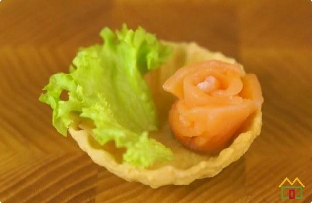 выкладываем в тарталетки кусочки салата и рыбу